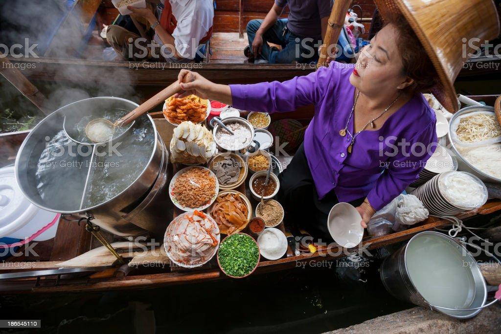 Food vendor at Damnoen Saduak Floating Market, Thailand. stock photo