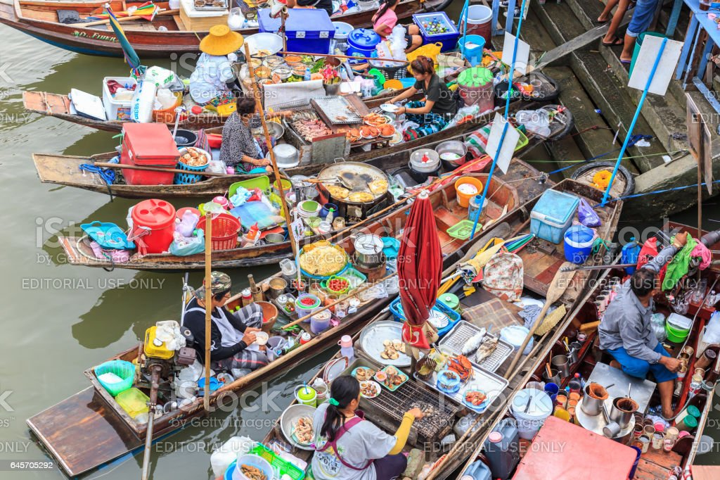 AMPHAWA, THAILAND - FEBRUARY 24 : Food vendors while working on boats in a place known as the floating market in Amphawa on February 24, 2017. Amphawa is a very popular tourist attraction in Thailand. stock photo