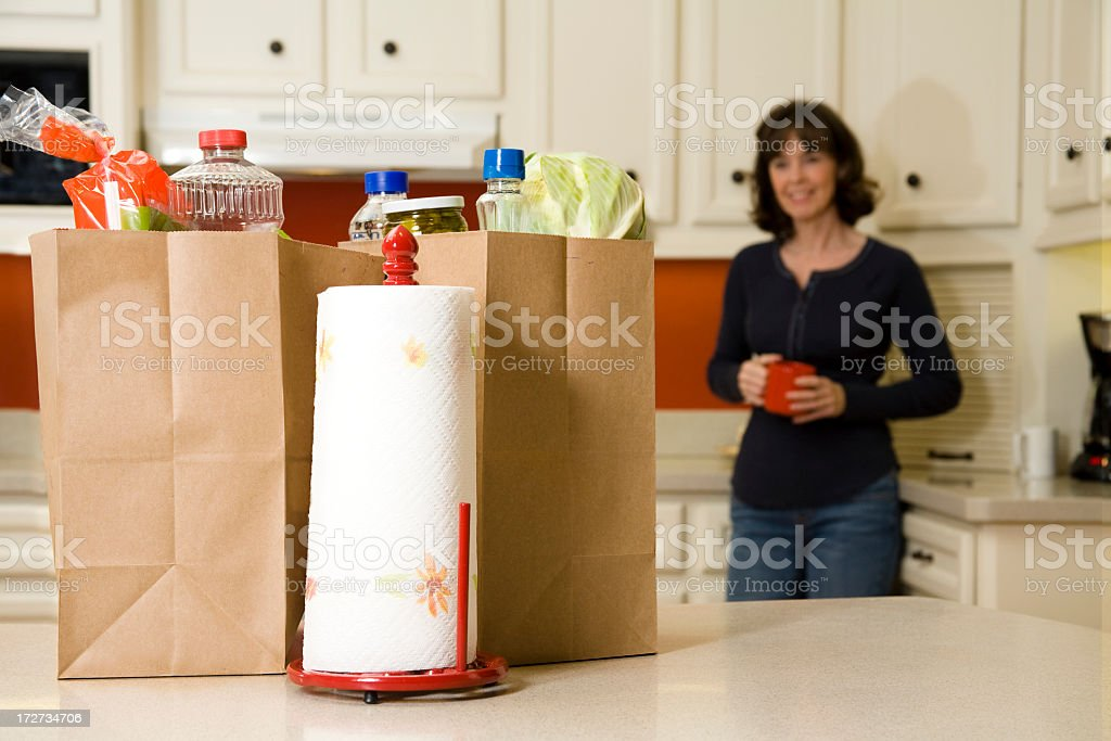 Food:  Woman looking at Grocery bags in the kitchen royalty-free stock photo