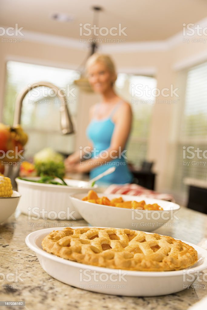 Food:  Woman prepares food in kitchen.  Pie foreground. royalty-free stock photo