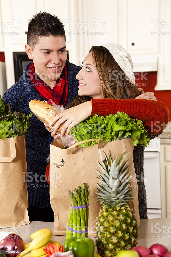 Food:  Young Latin couple in kitchen unpacking groceries vegetables. royalty-free stock photo