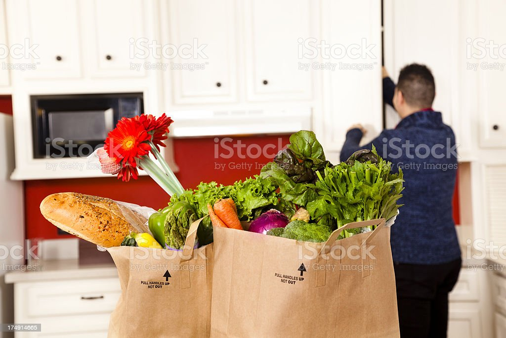 Food:  Young Latin man in kitchen putting away groceries vegetables. royalty-free stock photo