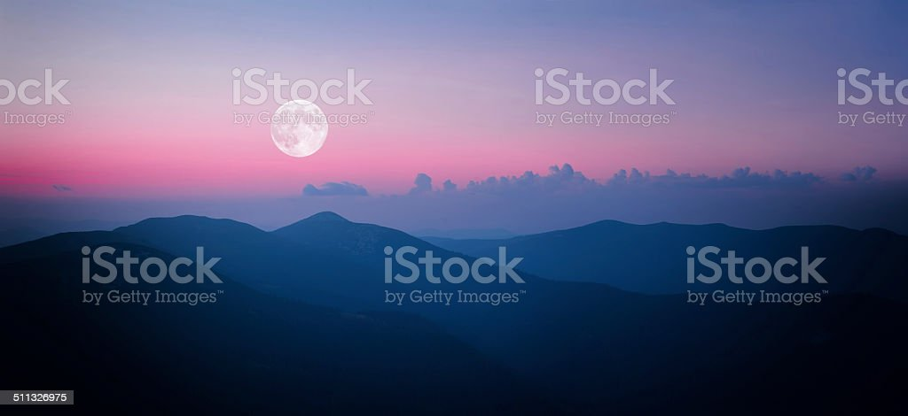 Fool moon rising over the mountain range stock photo