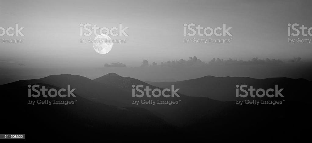 Fool moon rising over the mountain range stock photo