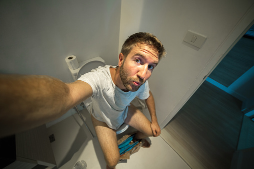 Happy Man Sitting In Public Restroom High-Res Stock Photo