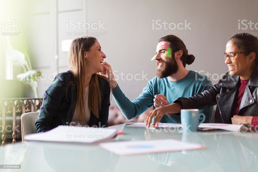 Fooling around with the adhesive notes in a business meeting. stock photo