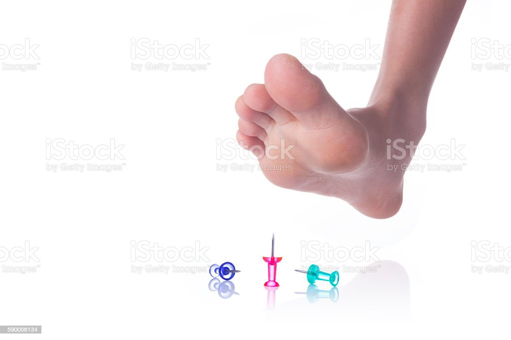 Foot about to step on sharp push pins stock photo