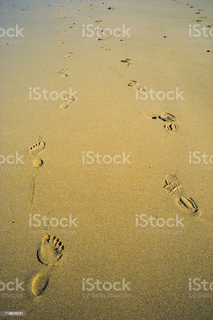 Foot and Boot Prints in Sand Together stock photo