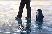 foot at lake ice surface. Winter sport, travel concept