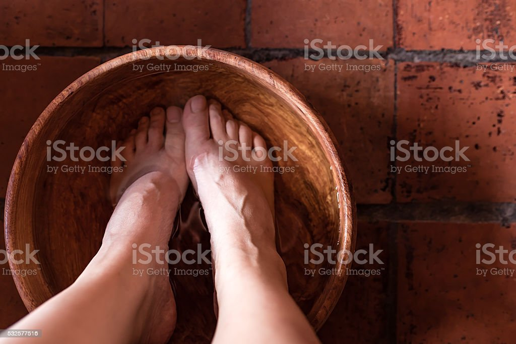 foot bath in a wooden bowl preparing for reflexology stock photo
