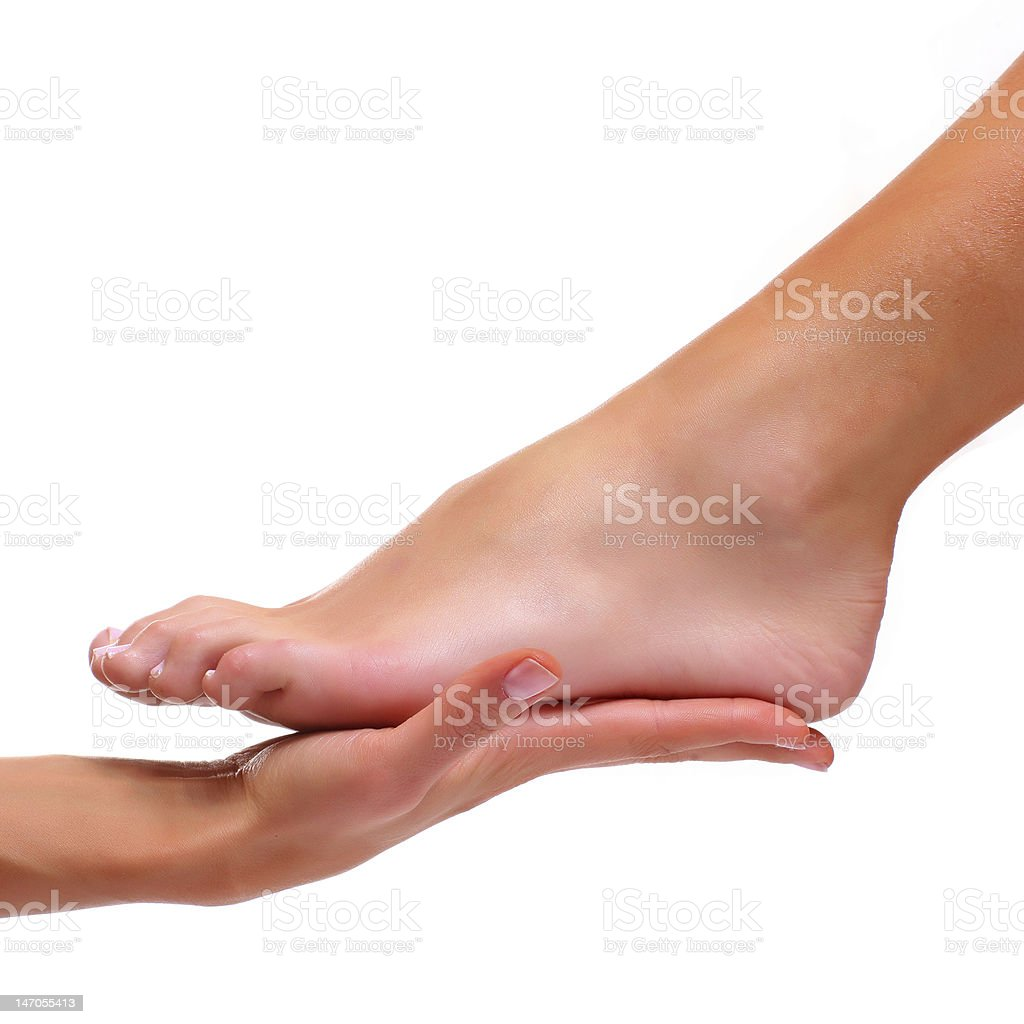 Foot being held in palm of hand isolated on white stock photo
