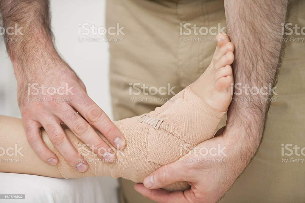 Foot being strapped by a doctor royalty-free stock photo
