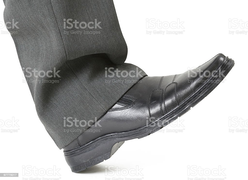 Foot in a shoe ready to crush stock photo