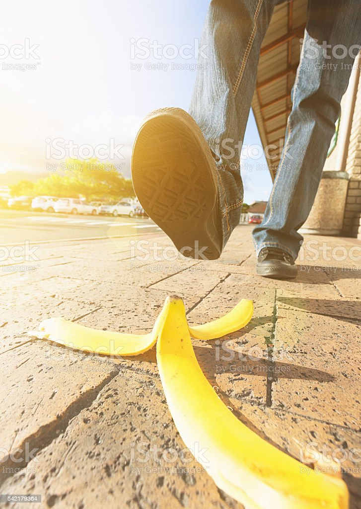 Foot in sneaker approaching dangerous dropped banana peel, accident ahead stock photo