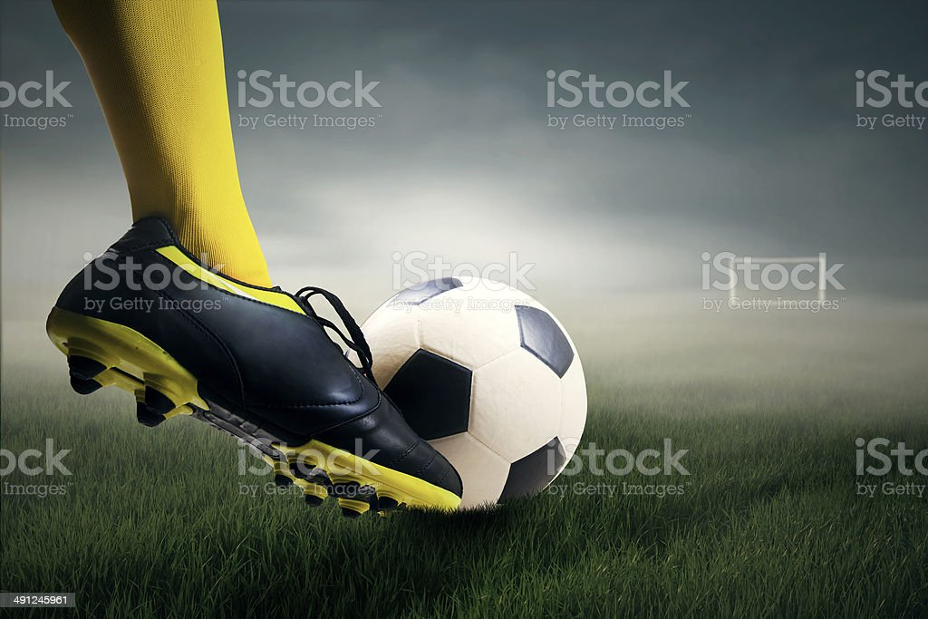 Foot kicking soccer ball stock photo