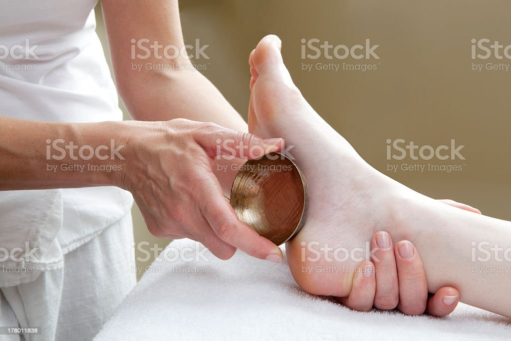 foot massage with bronze bowl stock photo