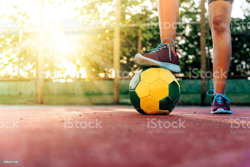 foot on soccer ball for kick off on hard court stock photo