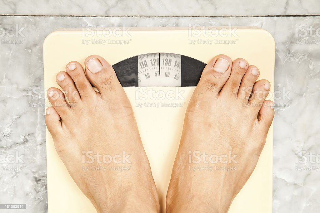Foot on the scales stock photo