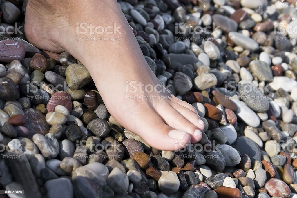 Foot over pebbles background royalty-free stock photo