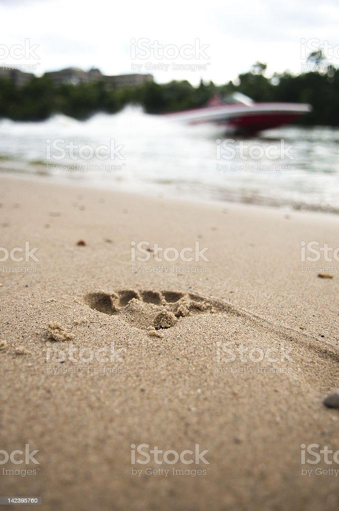 Foot Print in the Sand and Speed Boat stock photo