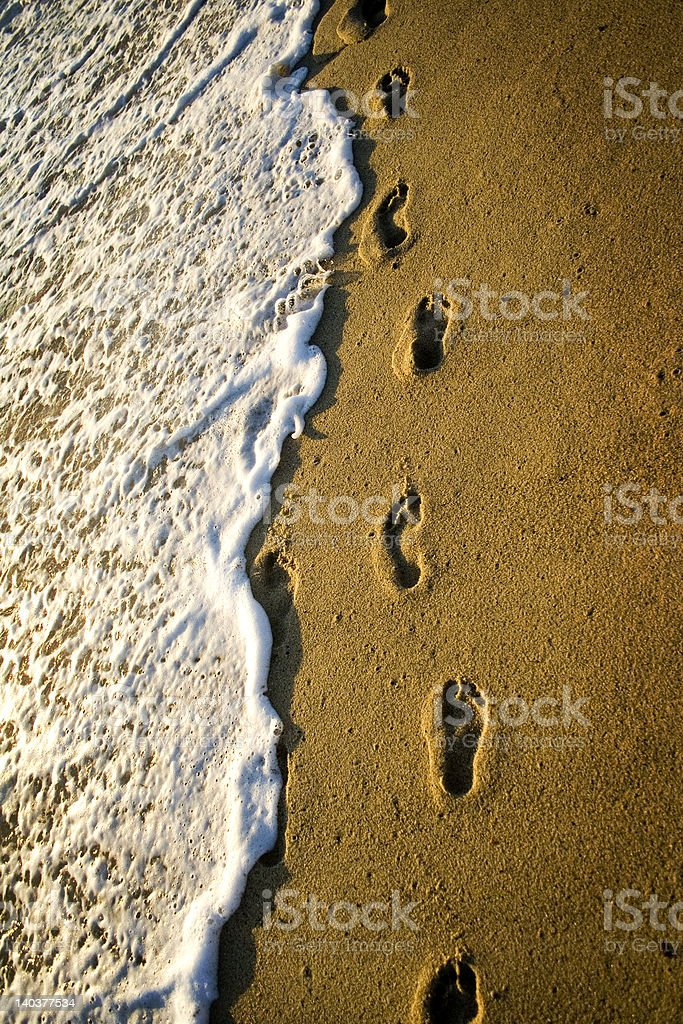 Foot Prints in Sand Washed Away by Wave royalty-free stock photo
