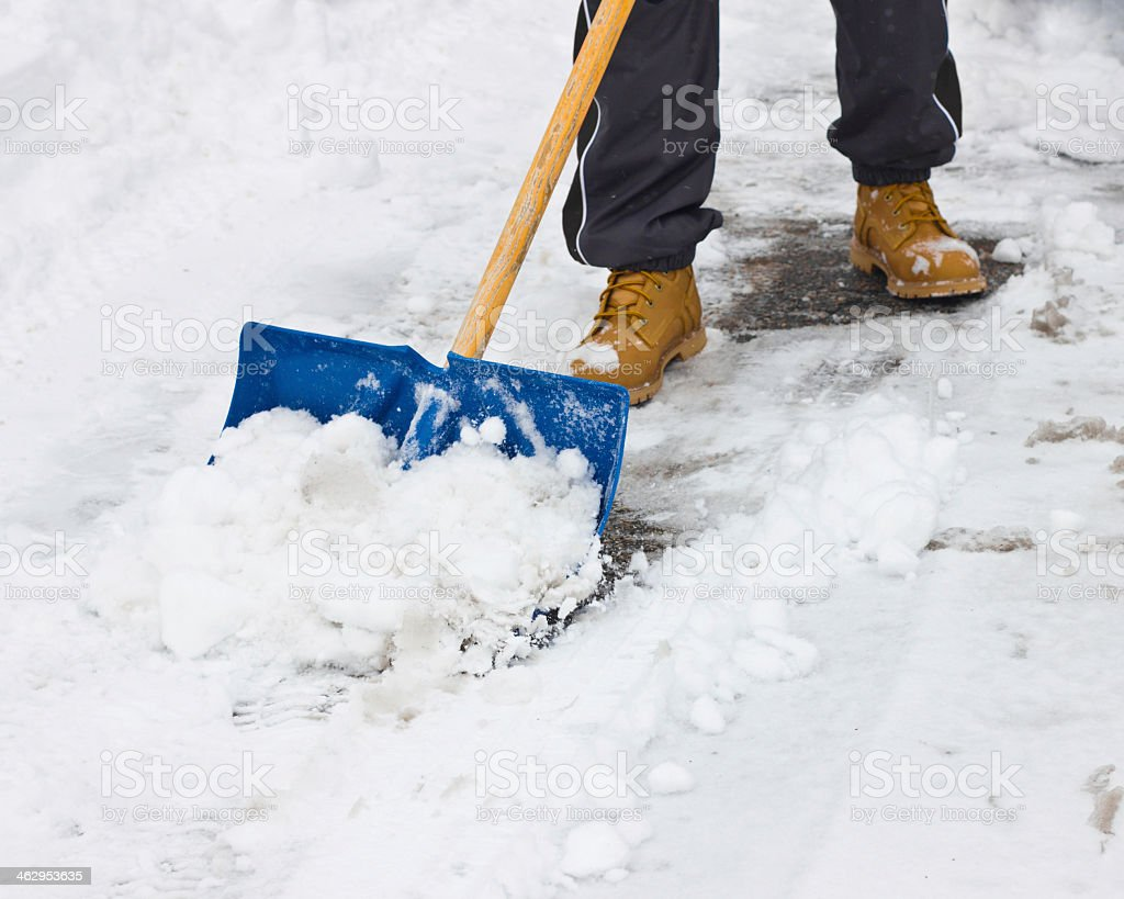 Foot shot of person shoveling snow with blue shovel stock photo
