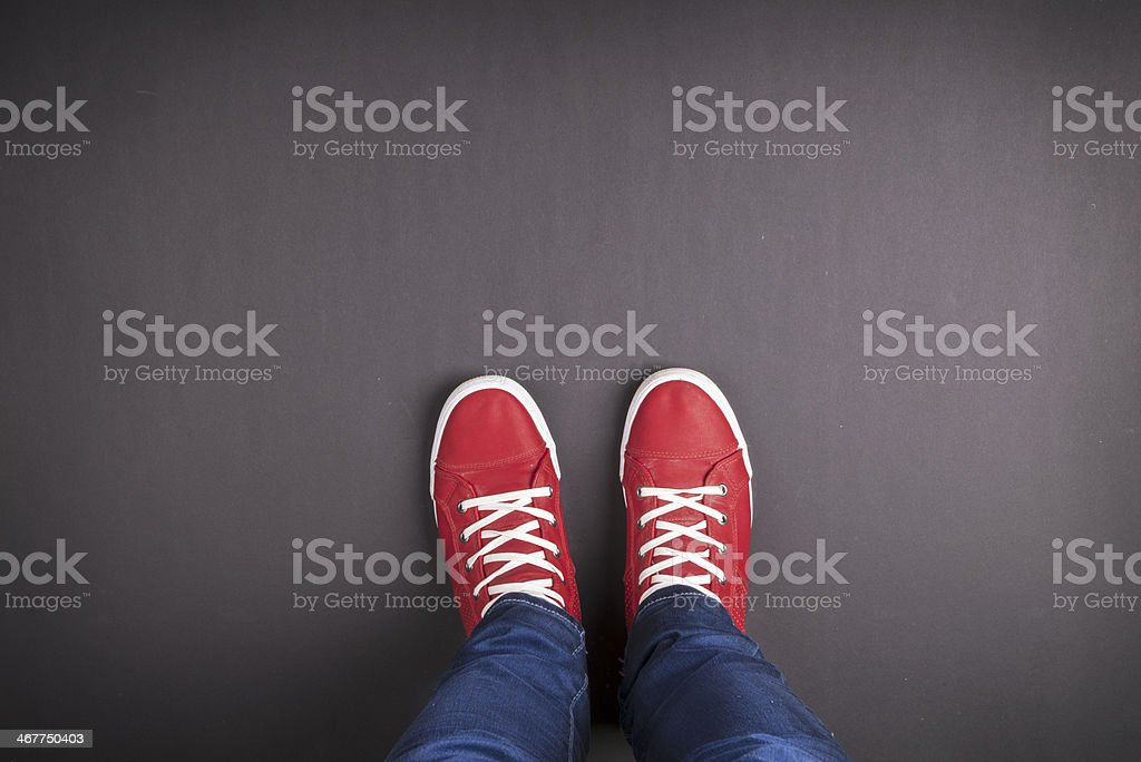 Foot shot with red sneakers on gray background stock photo