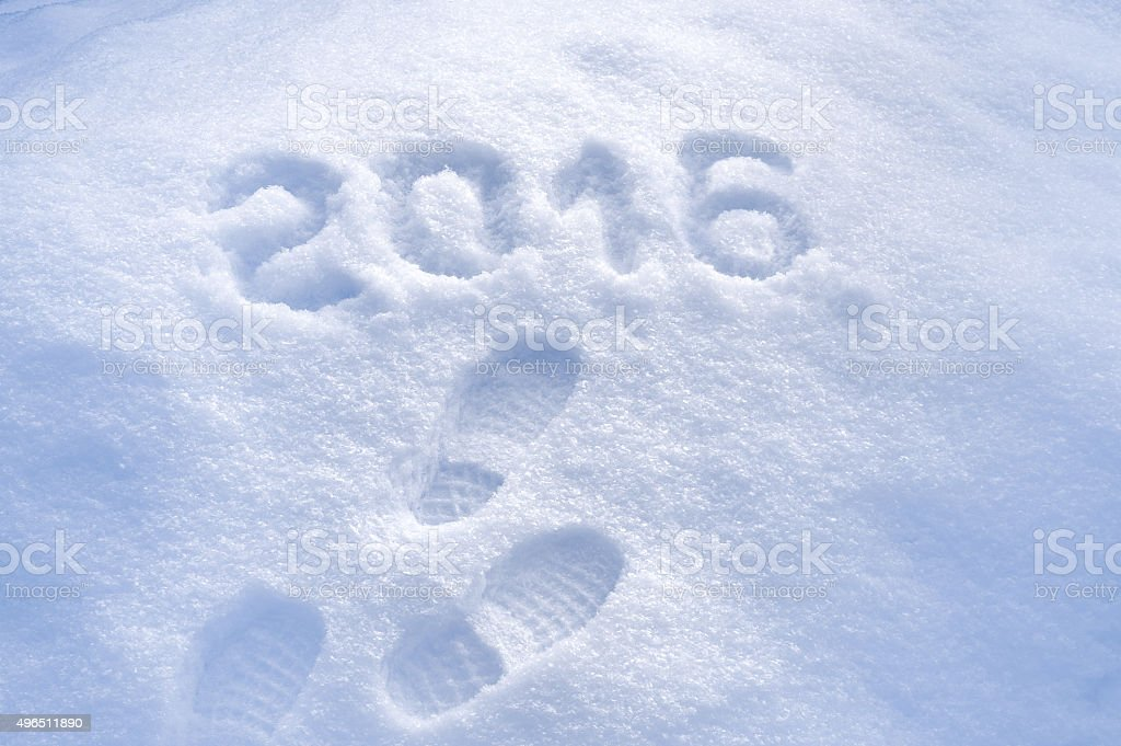 Foot step prints in snow, New Year 2016 greeting stock photo