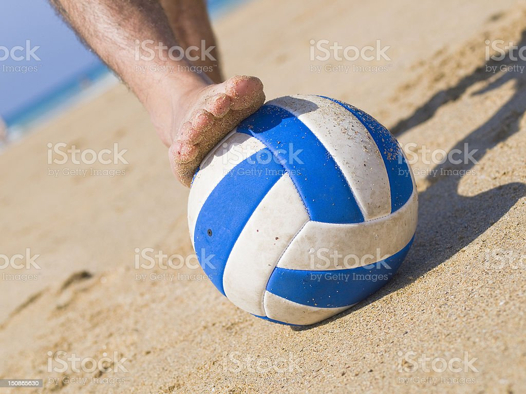 Foot stepping a ball on the beach 2 royalty-free stock photo