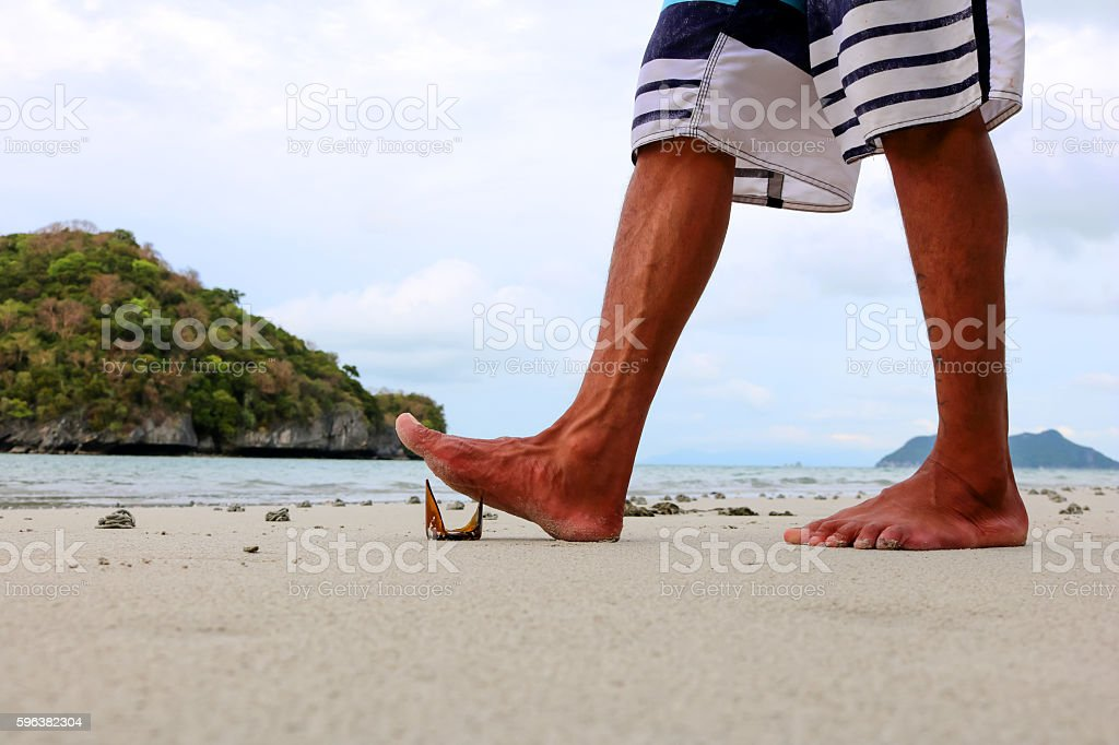 Foot stepping on broken bottles on the beach. stock photo