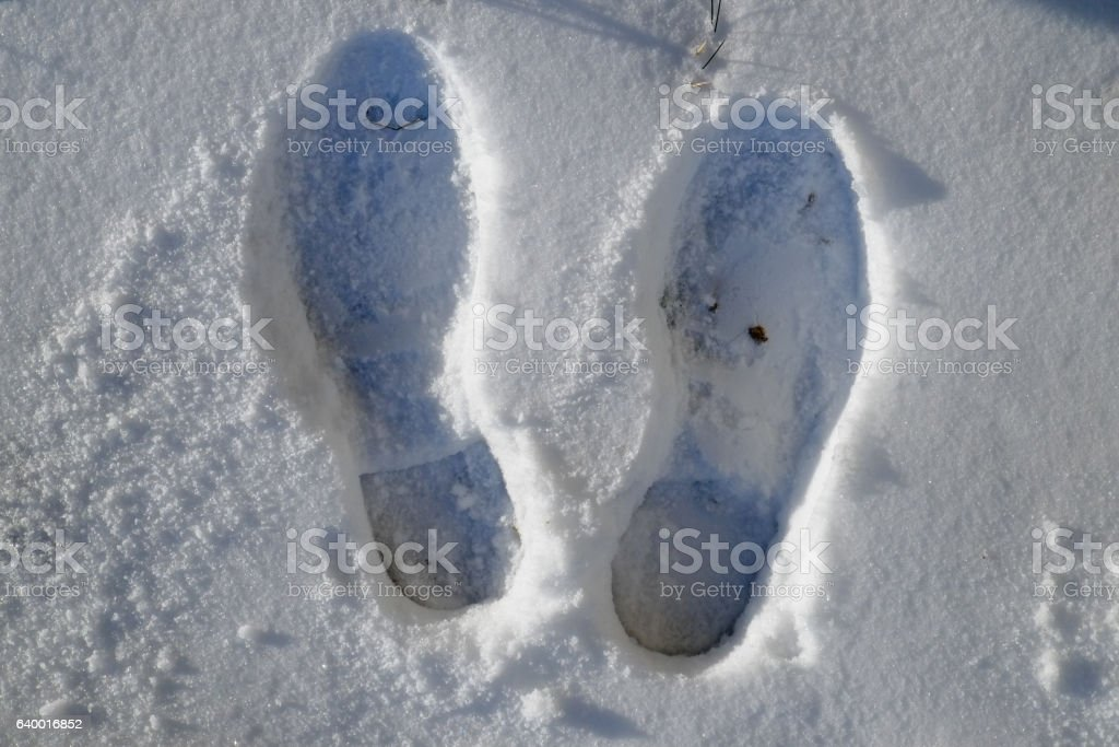 foot steps on snow ground on fresh snowy winter day stock photo