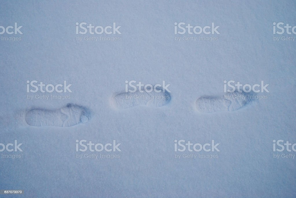 foot steps on snow ground snowy day of winter stock photo