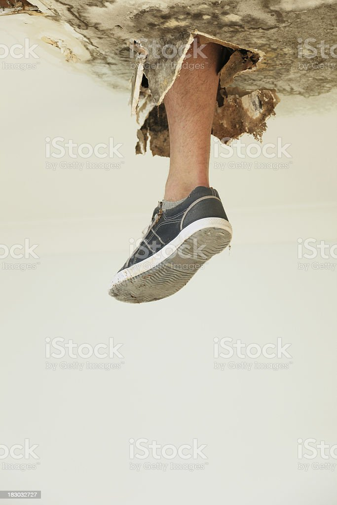 Foot through ceiling royalty-free stock photo