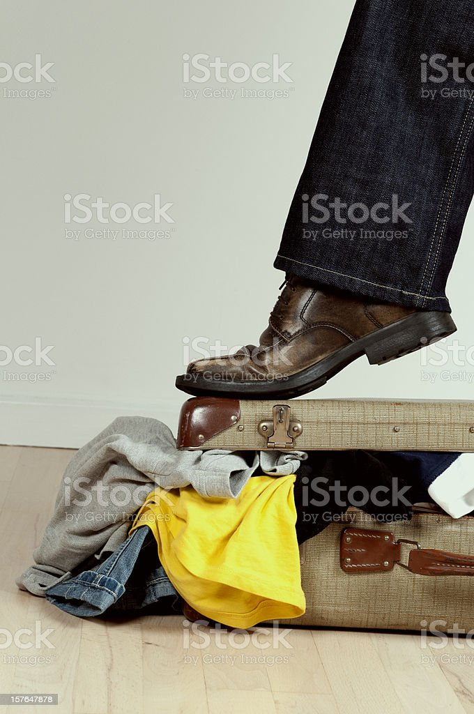 Foot tries to close retro style suitcase stuffed with clothes royalty-free stock photo