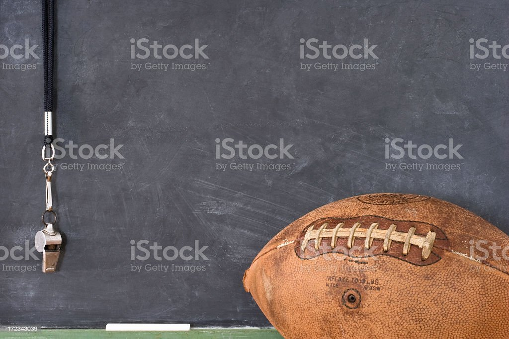 Football and a whistle against a blackboard stock photo