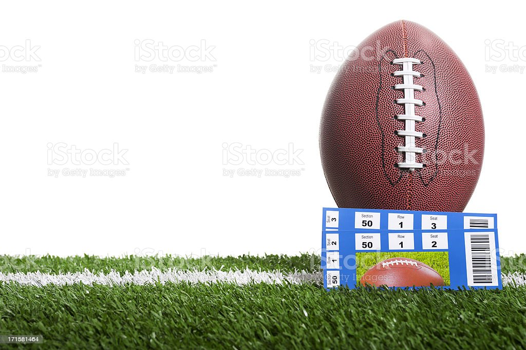 Football and game tickets on field with a white backdrop stock photo