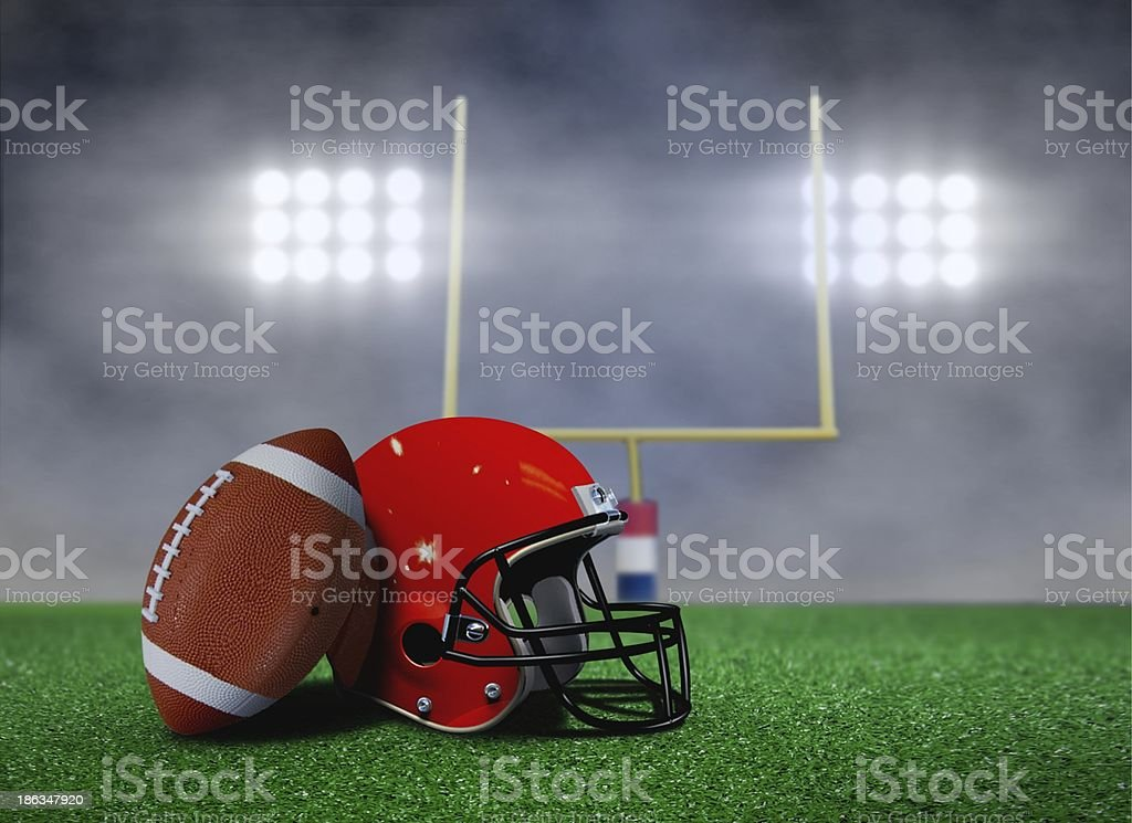 Football and Helmet on Field with Goal Post under Spotlights stock photo