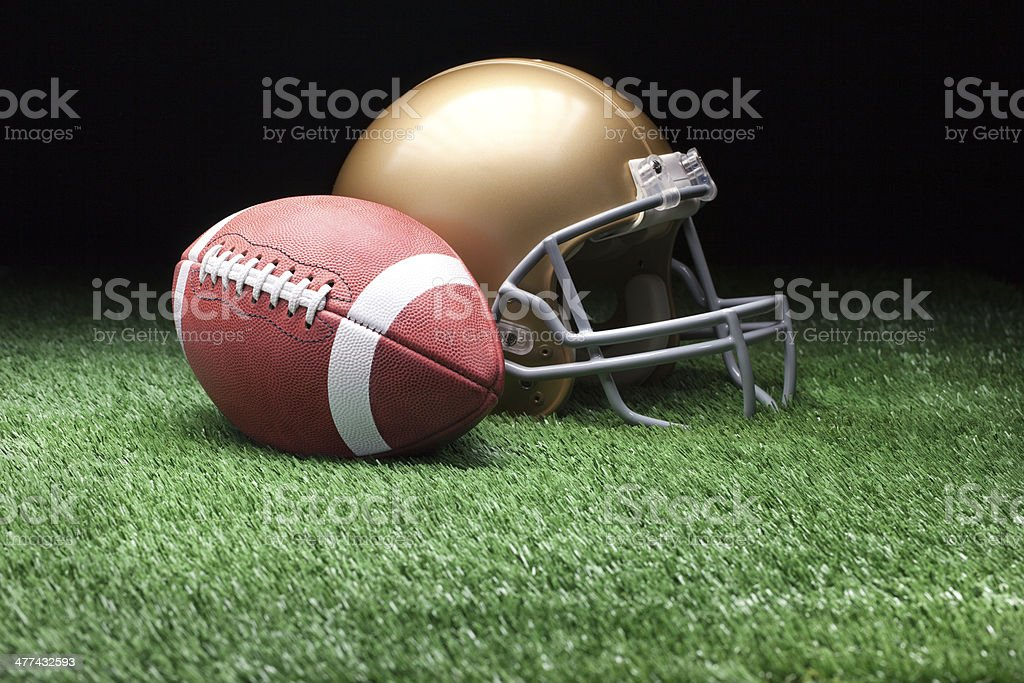 Football and helmet on grass against dark background stock photo