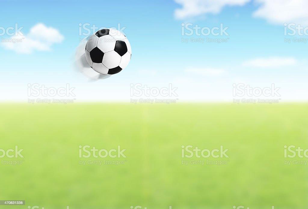 Football ball flying over field stock photo