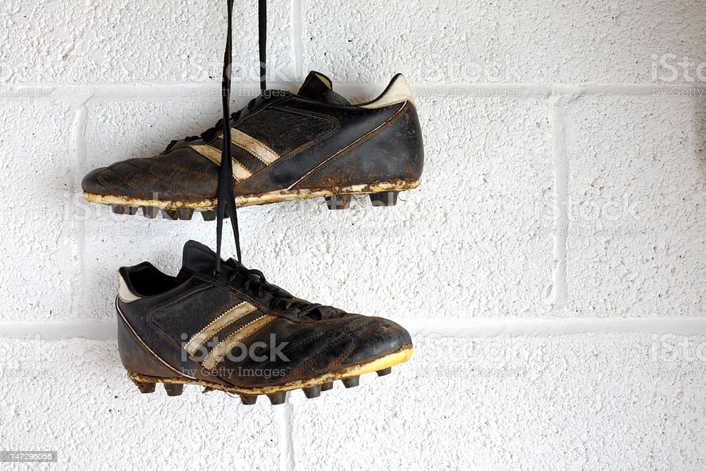 Football boots hang in a changing room stock photo
