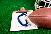 Football coach's whistle, football, player's helmet on green turf.