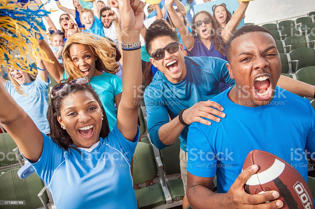 A large group of young adult football fans in outdoor stadium seats...