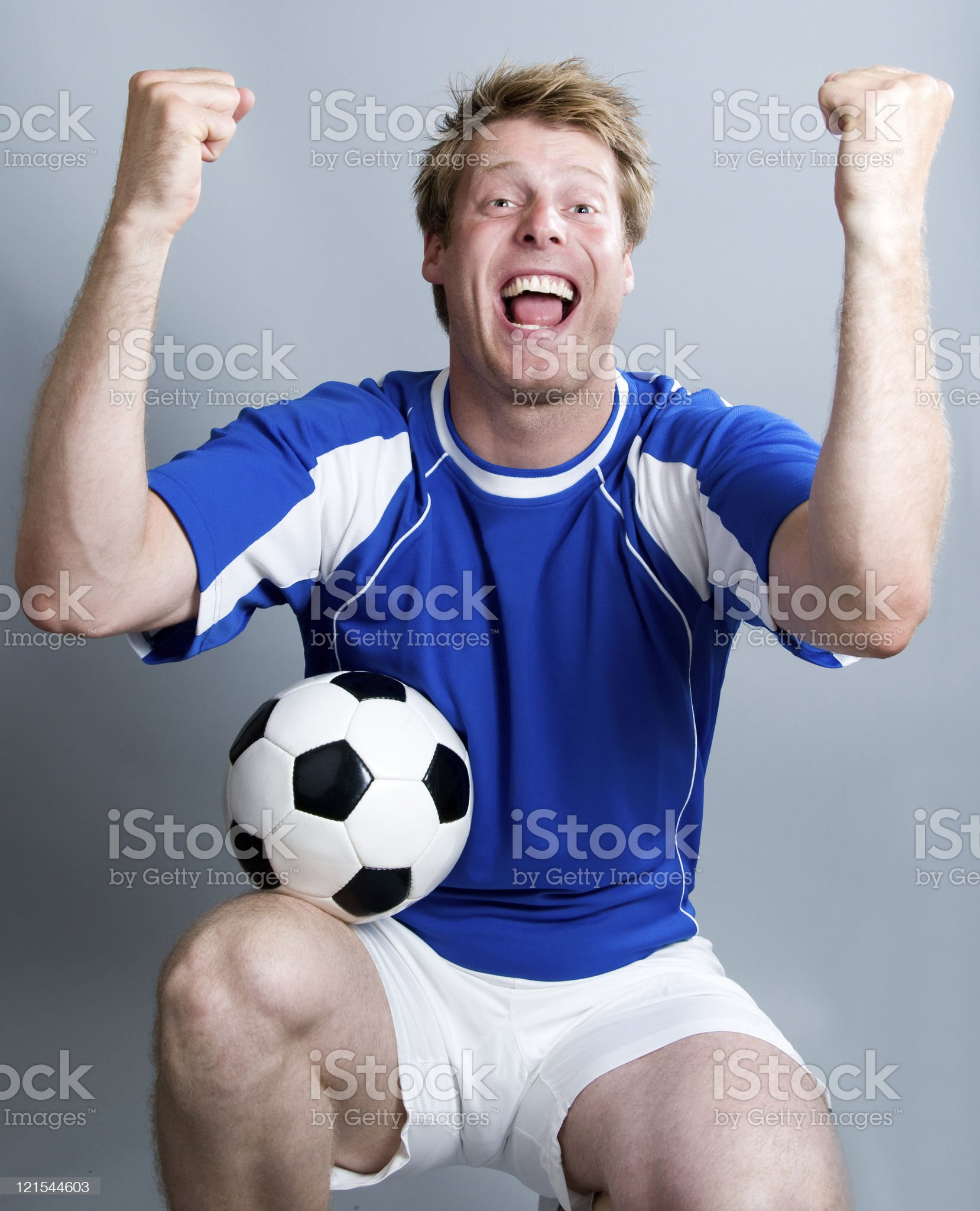 Football fan cheers and throws his hands in the air royalty-free stock photo