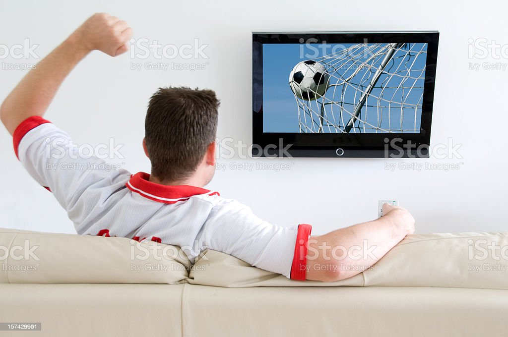 Football fan watches soccer on tv and cheers royalty-free stock photo
