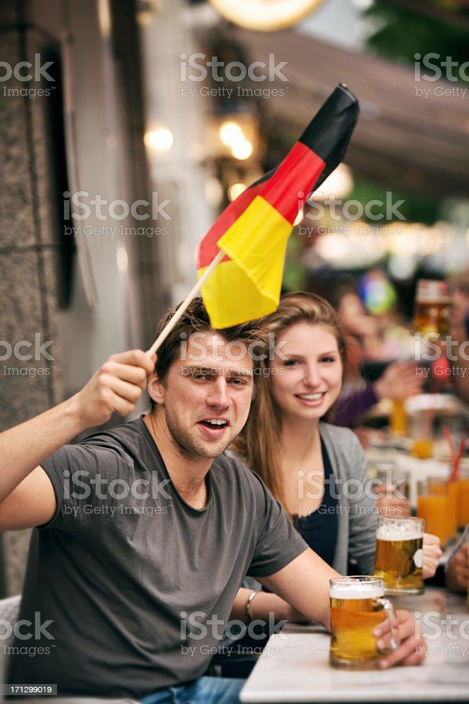 Football fans 0n sidewalk bar royalty-free stock photo