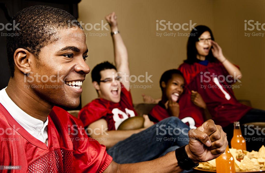 Football fans at home watching, cheering. Sports game on television. stock photo