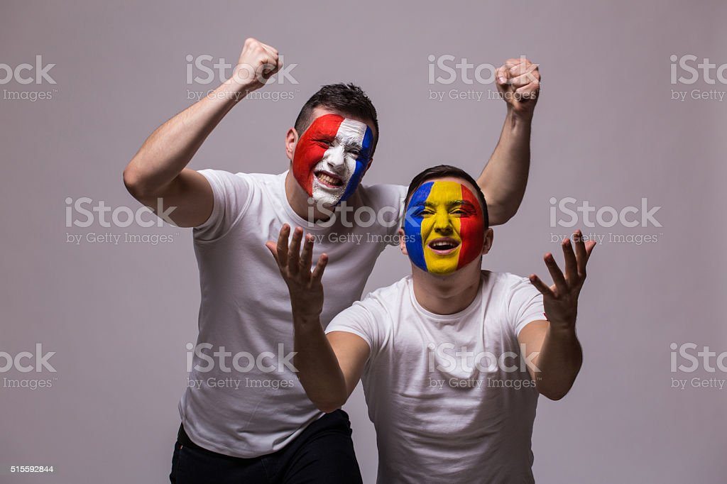 Football fans  national teams demonstrate emotions: Romanian lose, France win. stock photo