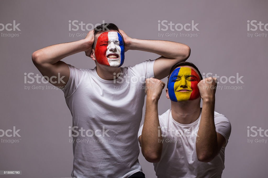 Football fans national teams demonstrate emotions: Romanian win, France lose. stock photo