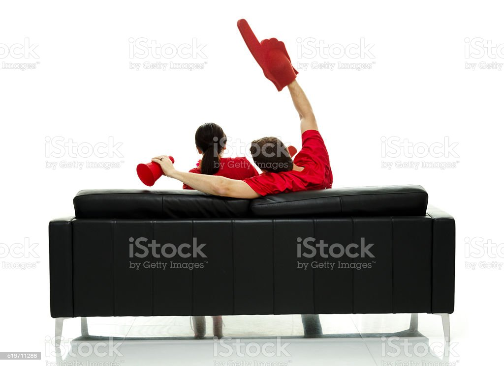 Football fans on couch and cheering stock photo