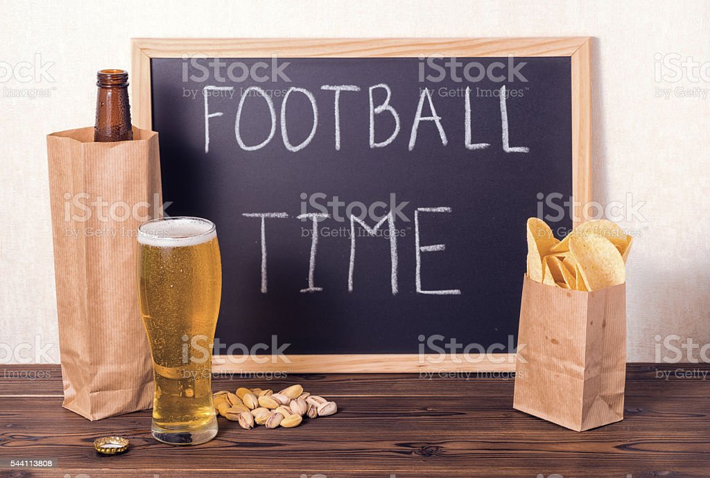 football fans setting of beer bottle in brown paper bag, stock photo